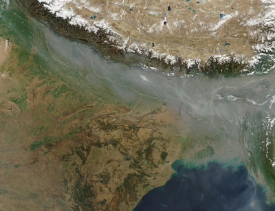 A pale band of haze hangs along the front of the Himalaya Mountains in Nepal, India, and Bangladesh in this photo-like image, taken on February 5, 2006, by a NASA satellite.