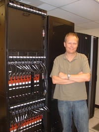 Thomas Girke, the director of UC Riverside's Bioinformatics Facility, stands next to Biocluster, a new supercomputer the campus has acquired.  Photo credit: UCR Strategic Communications.