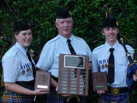 Pipe Band members Erin Thomson and Marshall German celebrate their first-place tie in a solo piping competition over Labor Day weekend. Holding the plaque they will share is Pipe Major Mike Terry.