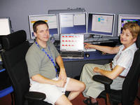 UCR's Robert Stringer and Gail Hanson near a beam monitor display in the CMS Control Room at CERN, just after Beam 2 made the first complete turn around the LHC. Stringer implemented the beam monitor display.  Photo credit: Hanson lab, UC Riverside.<br />