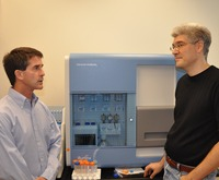 To sequence the barley genome, Timothy Close (left) and Stefano Lonardi (right) will use UCR's Illumina Genome Analyzer 2G, seen between them, which can generate billions of bases of high-quality DNA sequences per run. New sequencing technologies have broad applications in plant sciences and agriculture. Photo credit: UCR Strategic Communications. (Additional photo below.)