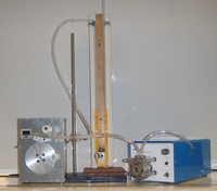 A smoking machine.  From left to right: a puffer box, a manometer, and a pump.<br />