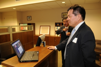 Consul General Jae Soo Kim checks a computer in the new Young Oak Kim Center for Korean American Studies.<br />