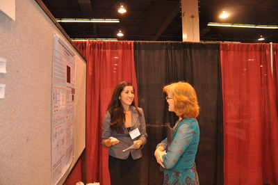 A student explains her research to Connie Nugent (right), an associate professor of cell biology at UCR and a judge at SACNAS.  Photo credit: UCR Strategic Communications.