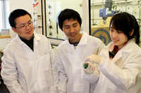 Yadong Yin (left), Le He (center) and Yongxing Hu examining a solution of iron oxide particles that changes color when an external magnetic field is applied to it.  Photo credit: Yin lab, UC Riverside.  (Another image below; also a video.)