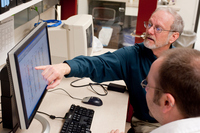 John H. Werren (pointing at computer screen) is a professor of biology at the University of Rochester, NY.  Photo credit: University of Rochester. (Another photo below.)