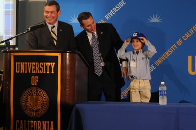 Vince Wickstrom tries on a UCR baseball cap as his father, Brian Wickstrom (center), is introduced to the campus and community. At left is UCR Chancellor Timothy P. White.