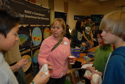 Mary Droser (center), a professor of in the Department of Earth Sciences and an organizer of the fair, talks to fairgoers about climate change. Photo credit: UCR Strategic Communications.