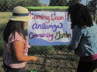 Volunteers put up signage telling community members about the Arlanza Community Garden at the corner of Cypress Ave. and Challen Ave. in Riverside. (Photo courtesy of Samantha Wilson, Child Leader Project)