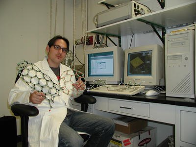 Daniel Perea of the Center for Nanoscale Science and Engineering, UCR, holds a molecular model of carbon nanotube (right hand) and a c60 molecule (left hand), while sitting in front of the screens of an atomic force microscope.  (Photo credit: CNSE, UC Riverside.)