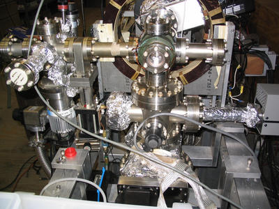 The ultra-high vacuum target chamber, where the intense positron pulse is implanted into the porous silica film. The magnet coils carry a current of 1000 amps for a few hundred milliseconds to generate the strong magnetic field needed to compress the positron beam.  Photo credit: D. Cassidy, UCR.