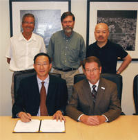 Signing the agreement at UCR to establish the CAU-UCR International Center for Ecology and Sustainability.  Front row, left to right: Zhangliang Chen, president of China Agricultural University; and UCR Acting Chancellor Robert D. Grey. Back row, left to right: UCR's Charles F. Louis, Donald Cooksey, and Bai-lian (Larry) Li.<br />