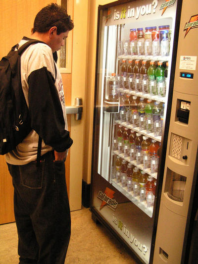 Jose Sanchez ponders a selection of bottled beverages in a vending machine in the Rivera Library.