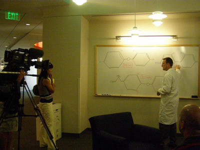 UCR's Cary Coburn explaining how PBDEs (polybrominated diphenyl ethers) closely resemble the molecular structure of PCBs (polychlorinated biphenyls) to a KNBC crew.  Photo credit: Curras-Collazo lab, UCR.