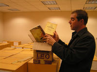 Justin McDaniel, assistant professor of religious studies, examines two of the nearly 14,000 Thai-language books obtained from a private collector in Bangkok.