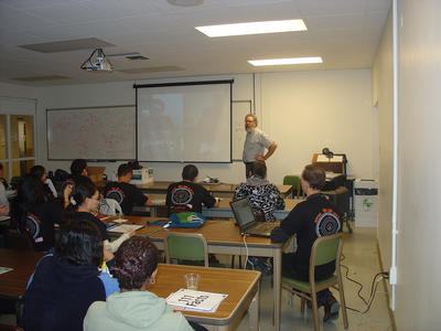 Robert Clare, a professor of physics, helps facilitate a videoconference, March 5, which connected San Jacinto High School students with their peers in Portugal.  The student groups shared their experiences doing particle physics experiments.  Besides Clare, UCR physicists Bill Gary (seen seated at right) and Gail Hanson coached the San Jacinto High School students, with assistance from Maria Chiara Simani of the ALPHA Center. Image credit: UCR Strategic Communications.