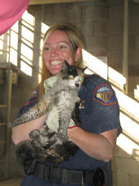 Michelle Rousseau of Riverside County Animal Services holds the cat after the rescue. (photo by Joan Kite)