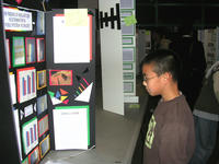 Forest Yang inspects a booth at last year's Riverside Unified School District Science and Engineering Fair.