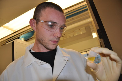 UC Riverside's Chris Reinhard studies a sample of pulverized black shale in solution. Photo credit: UCR Strategic Communications.