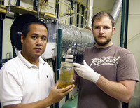CE-CERT development engineers Junior Castillo (left) and Eddie O'Neil (right) display the results of the steam hydrogasification process that converts urban waste feedstock (rear container) into clean synthetic diesel fuel (foreground container). The fuel was produced in the lab-scale reactor behind them.