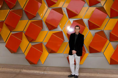Jim Isermann stands in front of the exterior sculpture at the Genomics Building.<br />