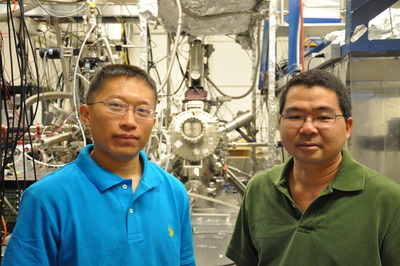 Wei Han (left) is a graduate student working in the lab of Roland Kawakami (right), an associate professor of physics and astronomy at UC Riverside.  The machine in the back is the molecular beam epitaxy chamber, where the researchers grew the titanium and the tunnel barriers.  Photo credit: UCR Strategic Communications.