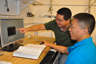 Wei Han (in blue shirt) and his advisor, Roland Kawakami, analyze data from their experiments.  Photo credit: UCR Strategic Communications.
