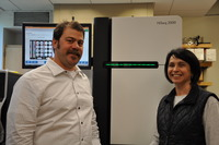 Photo shows Jason Stajich (left) and Susan Wessler before a Solexa/Illumina HiSeq2000 instrument at UC Riverside that they and their colleagues will use to sequence the genomes and measure the gene expression of several rice varieties.  Photo credit: UCR Strategic Communications.