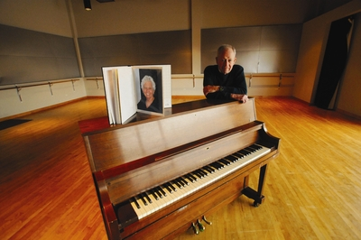 Robert Rosenthal stands at a piano in the dance studio at UC Riverside that bears the name of his late wife, MaryLu Clayton Rosenthal.