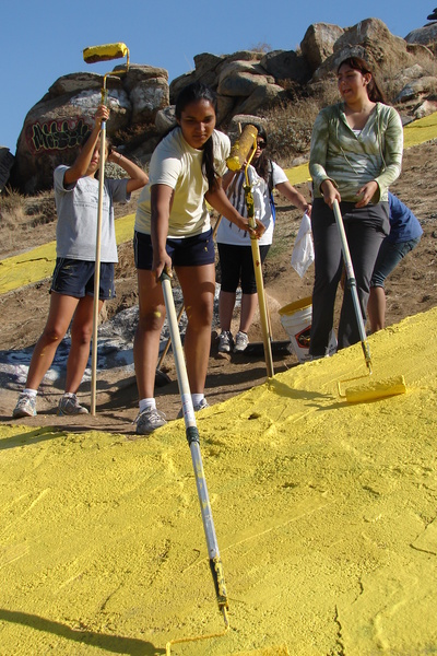 Volunteers use rollers to apply the yellow paint to the