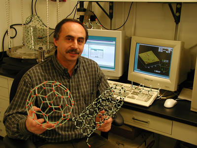 Misha Itkis of the Center for Nanoscale Science and Engineering, UCR, holding the same models - the atomic force microscope is visible in the background. (Photo credit: CNSE, UC Riverside.)