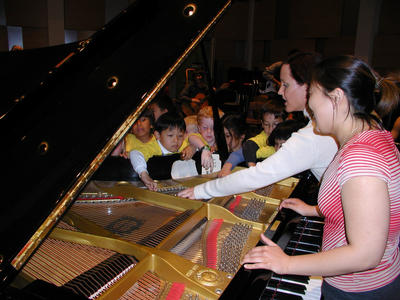 Gluck Fellows allow children to peer into the piano. At the piano are Gluck Undergraduate Music Fellow Joon Young Kim and Gluck Department Coordinator for Music Renee Coulombe